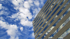 Building with reflections of clouds. Windows on a office building reflect clouds and blue skies Royalty Free Stock Photo