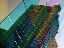Building reflections in colourful glass windows. Colourful glass panels reflect a building in the city center stock image