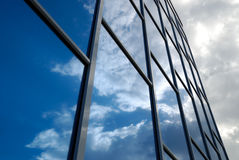 Building reflects the sky. The facade of a modern building from blue glass reflects the sky Stock Image