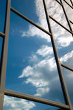 Building reflects the sky. The facade of a modern building from blue glass reflects the sky Stock Photo