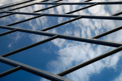 Building reflects the sky. The facade of a modern building from blue glass reflects the sky Stock Images