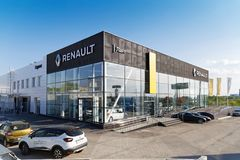 Building of Renault car selling and service center. Ulyanovsk, Russia - May 17, 2018: Building of Renault car selling and service center with signs against blue royalty free stock photo