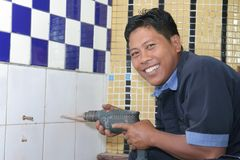 Building repair. Construction man drilling wall smiling Stock Photography