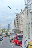 Building restoration. A building being restored or repaired, with cranes overhead Stock Image