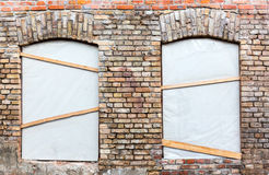 Building restoration. Closed windows on weathered brick wall - renovation Royalty Free Stock Photos