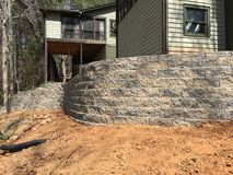 Building a Retaining Wall on the Back of a House. The back of a house showing the porches and a newly installed block retaining wall. The beginning of a royalty free stock images