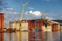 Building a road bridge across river. Construction of a new road bridge across the Yenisei River in Krasnoyarsk, Russia Royalty Free Stock Photography