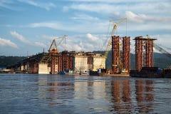 Building a road bridge across river. Construction of a new road bridge across the Yenisei River in Krasnoyarsk, Russia Royalty Free Stock Photos