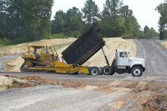 Building roads. Highway construction,dump truck bringing crushed rock to packing machine Royalty Free Stock Photo