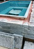 Building a rock encased spa and hot tub. Close up view of building a natural rock and stone wall for an outdoor spa and hot tub stock photo