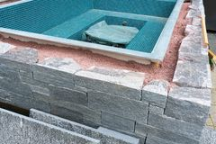 Building a rock encased spa and hot tub. Close up view of building a natural rock and stone wall for an outdoor spa and hot tub stock images