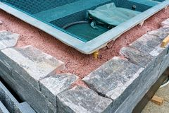Building a rock encased spa and hot tub. Close up view of building a natural rock and stone wall for an outdoor spa and hot tub royalty free stock photo
