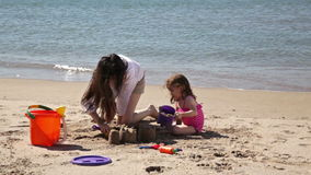 Building a sand castle together stock video