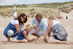 Building a sandcastle. Attractive young family building a sandcastle on the beach together Stock Photo