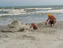 Building a sandcastle on a beach Royalty Free Stock Images