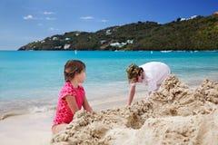 Building sandcastles. Brother & sister build sandcastles on the beach Stock Photos