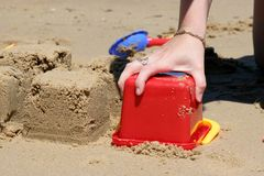 Building Sandcastles on Beach. Close up of person building sandcastles on beach with red plastic bucket Stock Images