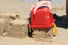Building Sandcastles on Beach. Close up of person building sandcastles on beach with red plastic bucket Royalty Free Stock Images