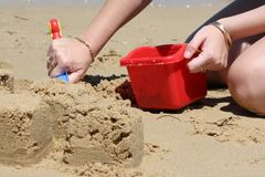 Building Sandcastles on Beach. Close up of person building sandcastles on beach with red plastic bucket Stock Photo