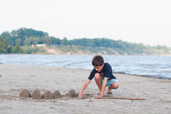 Building sandcastles. Young boy on a sandy beach building sandcastles by the water Stock Image