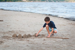 Building sandcastles. Young boy on a sandy beach building sandcastles by the water Stock Photography