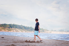 Building sandcastles. Young boy on a sandy beach building sandcastles by the water Stock Photos