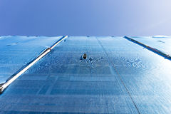 Building with scaffolding draped in blue debris netting Royalty Free Stock Photo