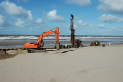 Building sea defences. An orange digger and a pile driver prepare improvements to Lancashire's sea defences Stock Image