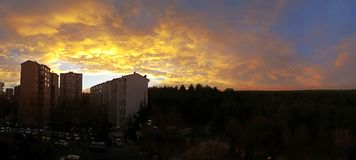 A Building Silhouette at Sunset with Clouds. A panoramic view of evergreen forest and building silhouette stock image