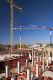 Building site. Bulding site with concrete columns and tower cranes set against a vivid ble sky Royalty Free Stock Image