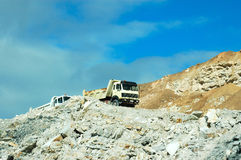Building site. A lonely building site with working trucks destroying nature on a rocky hill on a sunny summer day in South Africa Royalty Free Stock Photo