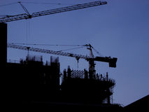 Building site 3. Silhouette of building site with 2 cranes and men climbing scaffolding royalty free stock photo