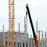 Building site. Closeup of the arm of a crane working on support beams at a building construction site Stock Photos