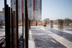 The building site against the background of a multistorey building. Two builders are working royalty free stock images