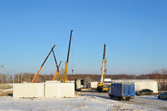 Building site. With crane trucks that unloads trucks and works on the construction stock image