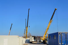 Building site. With the crane trucks that unloads trucks and works on construction royalty free stock photo