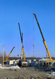Building site. With a crane trucks that unloads trucks and works on the construction royalty free stock image
