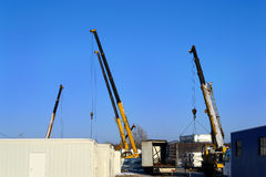 Building site. With crane trucks that unloads trucks and works on a construction royalty free stock image