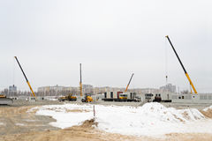Building site. With crane trucks that unloads trucks and works on construction in overcast weather royalty free stock photography