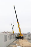 Building site. With crane trucks that works on construction in overcast weather royalty free stock photo