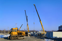 Building site. With excavator and crane trucks that unloads trucks and works on construction stock images