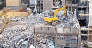 Construction site in england. Building site with heavy machinery knocking down a building to make way for something new Stock Images