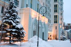 Building with snow-covered fir. Front porch of white multistorey building with two snow-covered firs on each side Royalty Free Stock Image