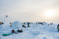 Building a snow igloo on the frozen sea. Competition for the construction of a snow igloo in Siberia royalty free stock photos