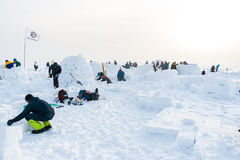 Building a snow igloo on the frozen sea. Competition for the construction of a snow igloo in Siberia stock photo