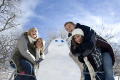 Building a Snowman. A group of young people enjoy a day playing in the snow and building a snowman. Copy space above Royalty Free Stock Image