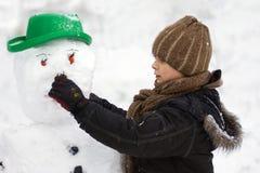 Building a snowman. Boy is building the snowman stock images