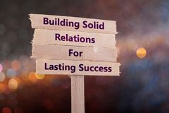 Building solid relations for lasting success. Wooden sign with boke background Royalty Free Stock Image