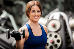 Building some muscle and smiling. Happy young brunette doing some bicep curls with dumbbells and smiling in a gym stock image
