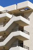 Building Staircase. The exterior staircase of a white, rectangular, concrete condominium building with a clear blue sky at the roofline Royalty Free Stock Photography